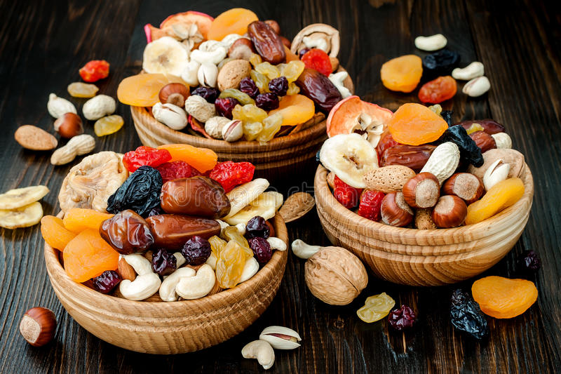 Mix of dried fruits and nuts on a dark wood background with copy space. Symbols of judaic holiday Tu Bishvat. Mix of dried fruits and nuts on dark wood stock photography