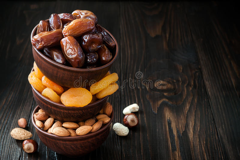 Mix of dried fruits and nuts on a dark wood background with copy space. Symbols of judaic holiday Tu Bishvat. Mix of dried fruits and nuts on dark wood royalty free stock photos