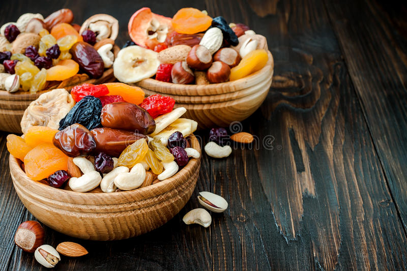 Mix of dried fruits and nuts on a dark wood background with copy space. Symbols of judaic holiday Tu Bishvat. Mix of dried fruits and nuts on dark wood stock photo