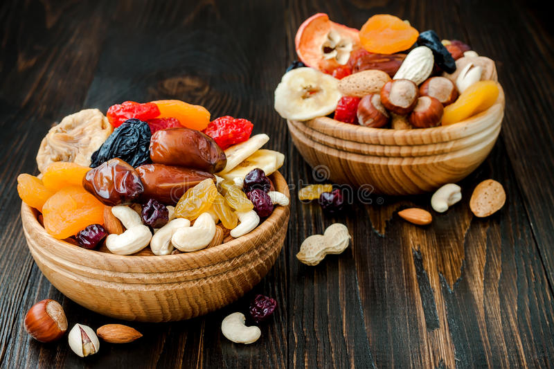 Mix of dried fruits and nuts on a dark wood background with copy space. Top view. Symbols of judaic holiday Tu Bishvat. Mix of dried fruits and nuts on dark stock photos