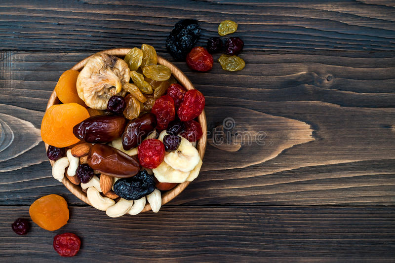 Mix of dried fruits and nuts on a dark wood background with copy space. Top view. Symbols of judaic holiday Tu Bishvat. Mix of dried fruits and nuts on a dark stock photography