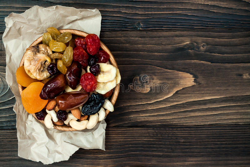 Mix of dried fruits and nuts on a dark wood background with copy space. Top view. Symbols of judaic holiday Tu Bishvat. Mix of dried fruits and nuts on a dark royalty free stock photography
