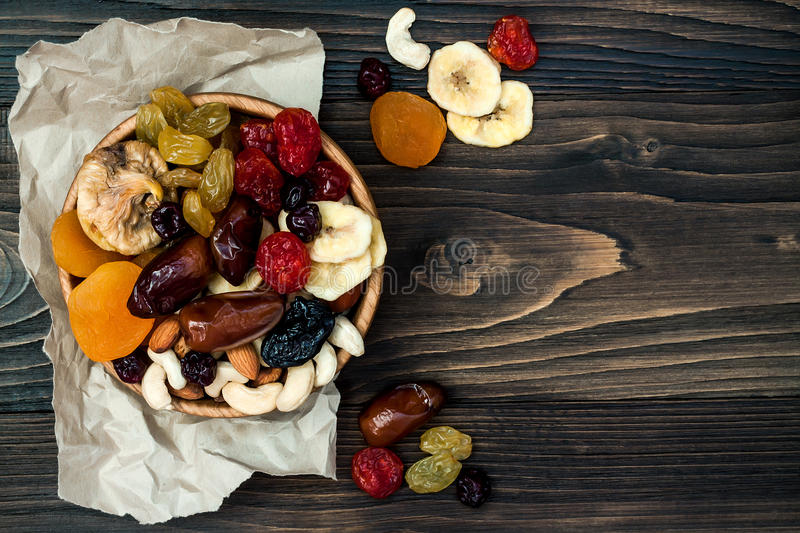 Mix of dried fruits and nuts on a dark wood background with copy space. Top view. Symbols of judaic holiday Tu Bishvat. Mix of dried fruits and nuts on a dark royalty free stock image