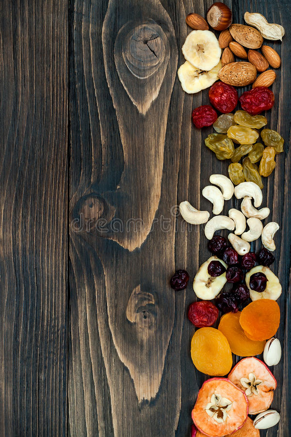 Mix of dried fruits and nuts on a dark wood background with copy space. Top view. Symbols of judaic holiday Tu Bishvat. Mix of dried fruits and nuts on a dark royalty free stock photo