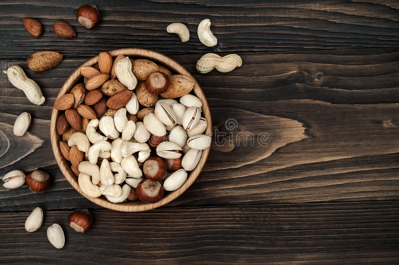 Mix of dried fruits and nuts on a dark wood background with copy space. Top view. Symbols of judaic holiday Tu Bishvat. Mix of dried fruits and nuts on a dark stock photo