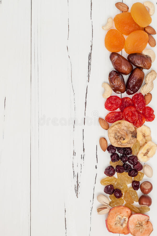 Mix of dried fruits and nuts on a white vintage wood background with copy space. Top view. Symbols of judaic holiday Tu Bishvat. Mix of dried fruits and nuts on stock photos