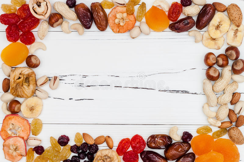 Mix of dried fruits and nuts on a white vintage wood background with copy space. Top view. Symbols of judaic holiday Tu Bishvat. Mix of dried fruits and nuts on stock image