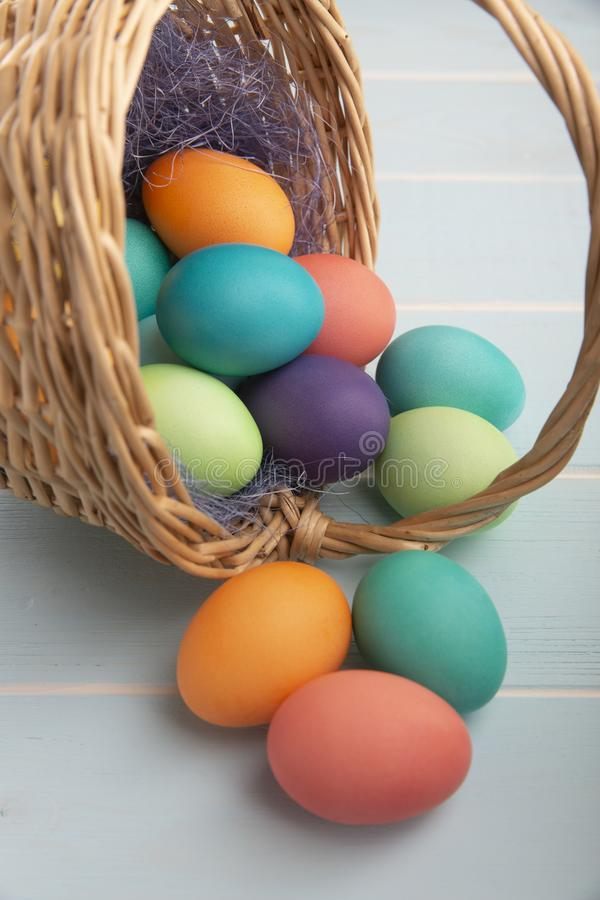 Mix of dyed bright Easter eggs in a withe basket with colorful blue sisal  on a wooden blue surface royalty free stock photos