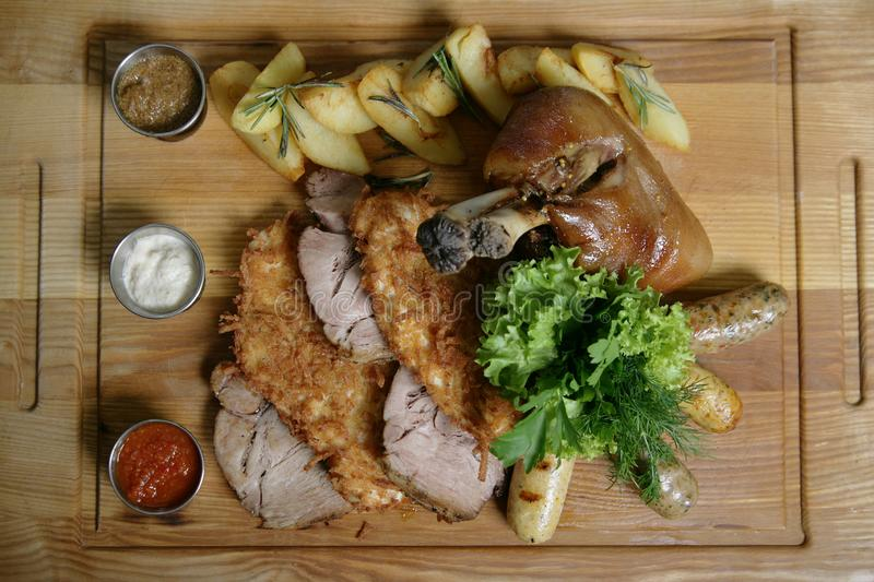 Mix food for a big company. A big delicious whole baked knuckle, fried meat chops, ham, potatoes. stock images