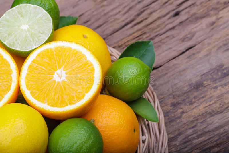 Mix of fresh citrus fruits in basket on wood stock photo