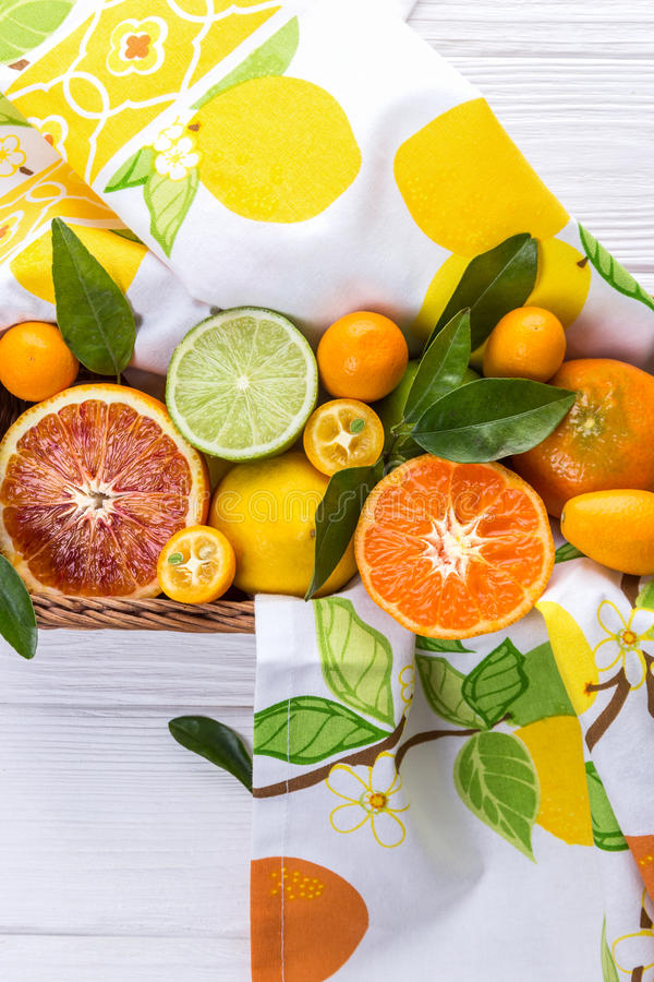 Mix of fresh citrus fruits with green leaves in basket. Orange, lemon, mandarin, lime, kumquat on white background royalty free stock images