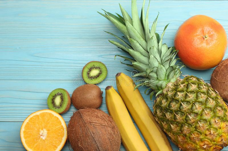 Mix of fresh coconut, banana, kiwi fruit, orange and pineapple on blue wooden background. top view with copy space stock photos
