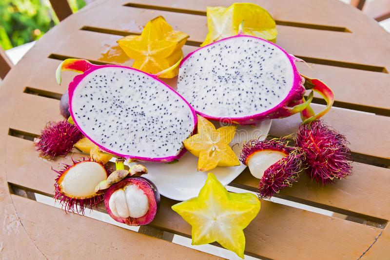 Mix of fresh fruits from Thailand, dragon fruit, rambutan, carambola, mangosteen up view. Sliced beautiful fresh tropical fruits.  stock photography