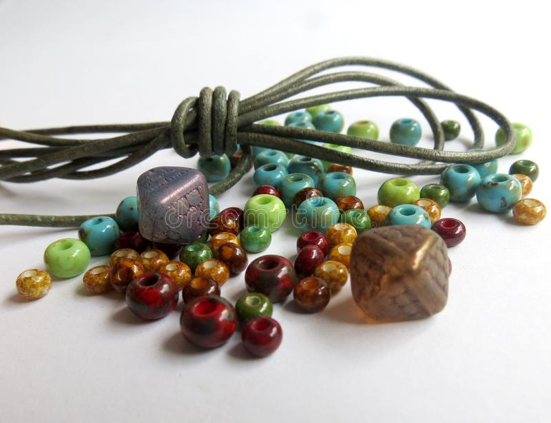 Mix of green, brown, mint and beige glass beads and green leather cord for hobbies including jewelry making and crafts. A mix of green, brown, mint and beige stock images