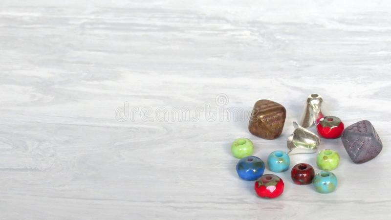 Mix of glass beads and jewelry supplies hobbies including jewelry making and crafts. Handmade jewelry. Mix of green, red, blue, purple, brown glass beads and stock photos