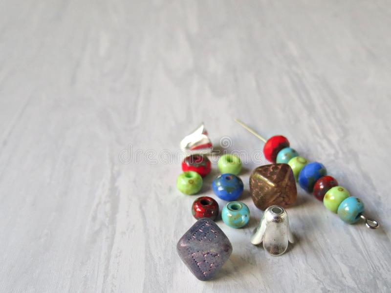 Mix of glass beads and jewelry supplies hobbies including jewelry making and crafts. Handmade jewelry. Mix of green, red, blue, purple, brown glass beads and stock images