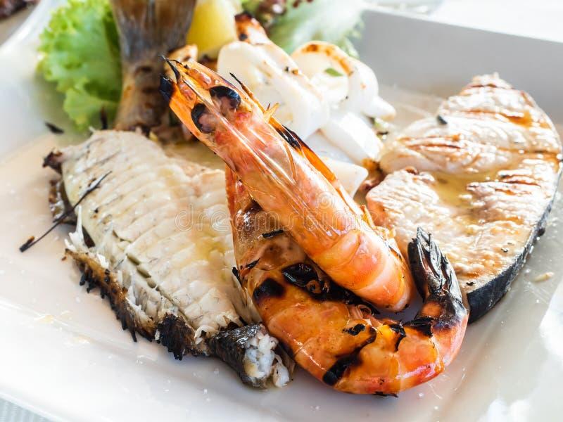 A mix of grilled fish, calamari, prawns, swordfish, with salad and lemon royalty free stock photo