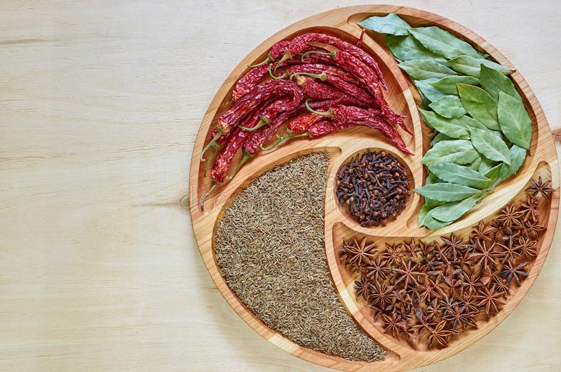 Mix of hot spices on the wooden plate: star anise, bay leaves, paprika, dried cloves and cumin close up. Spices texture background stock photos