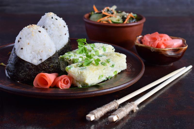 Mix of Japanese food - rice balls onigiri, omelette, pickled ginger, sunomono wakame cucumber salad and chopsticks. Asian. Breakfast or lunch background stock images