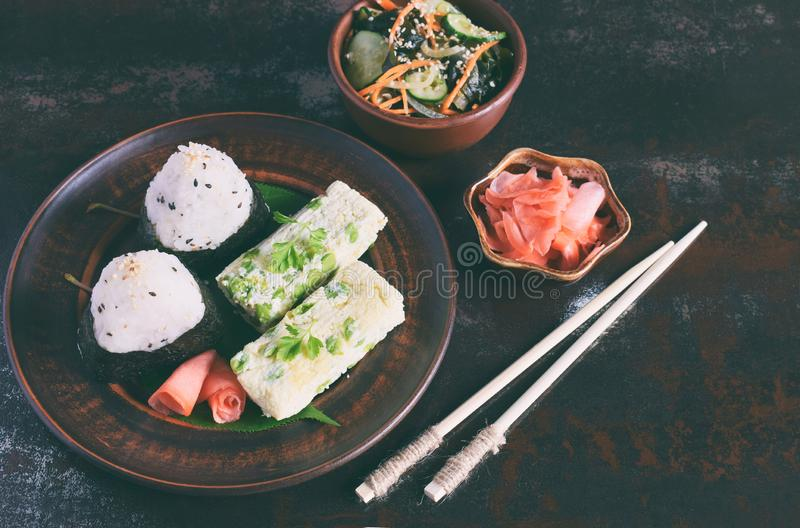 Mix of Japanese food - rice balls onigiri, omelette, pickled ginger, sunomono wakame cucumber salad and chopsticks. Asian. Breakfast or lunch background royalty free stock photos