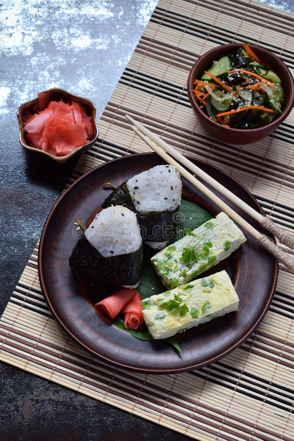 Mix of Japanese food - rice balls onigiri, omelette, pickled ginger, sunomono wakame cucumber salad and chopsticks. Asian. Breakfast or lunch background stock image