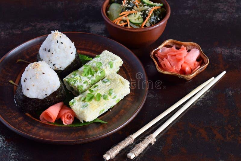 Mix of Japanese food - rice balls onigiri, omelette, pickled ginger, sunomono wakame cucumber salad and chopsticks. Asian. The mix of Japanese food - rice balls royalty free stock images