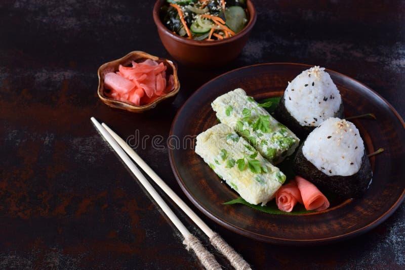 Mix of Japanese food - rice balls onigiri, omelette, pickled ginger, sunomono wakame cucumber salad and chopsticks. Asian. The mix of Japanese food - rice balls royalty free stock photo