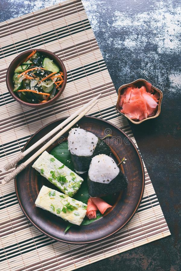 Mix of Japanese food - rice balls onigiri, omelette, pickled ginger, sunomono wakame cucumber salad and chopsticks. Asian. The mix of Japanese food - rice balls stock photos