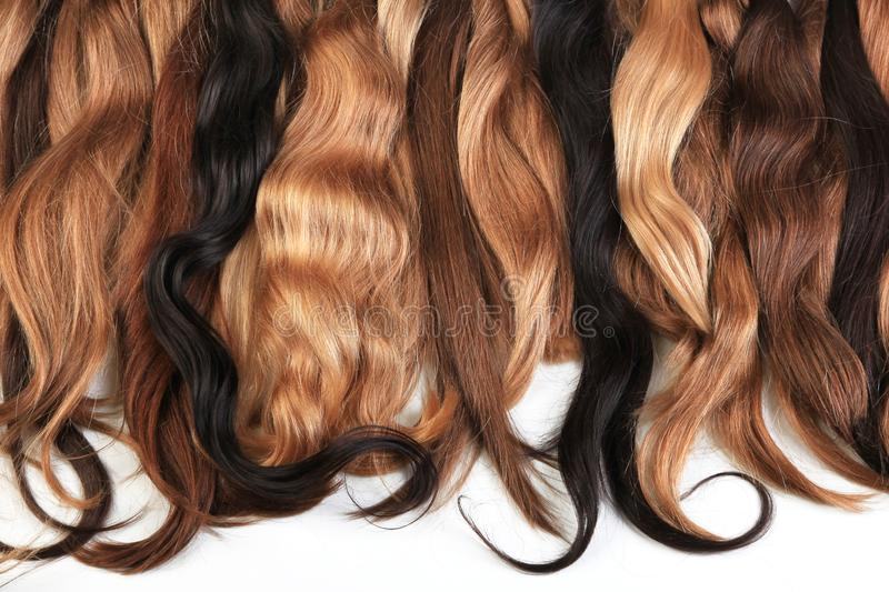 Mix of natural extensions hair: blond, red, brown. Strands of ha. Ir for hairstyles. Isolated on white background royalty free stock photos