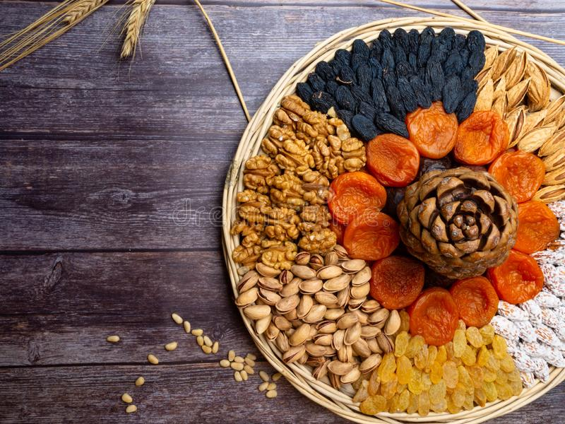 mix of nuts as walnuts, almond, cedar, pistachios, and dried apricots, blue and yellow raisin wheat cereal on wooden background stock images