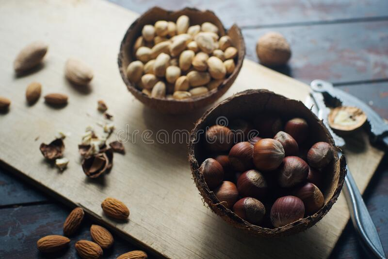 Mix of nuts in coconut bowls on dark wooden table, walnuts, almond, hazelnut, cashew, healthy various superfoods. Mix of nuts in coconut bowls and vintage stock images