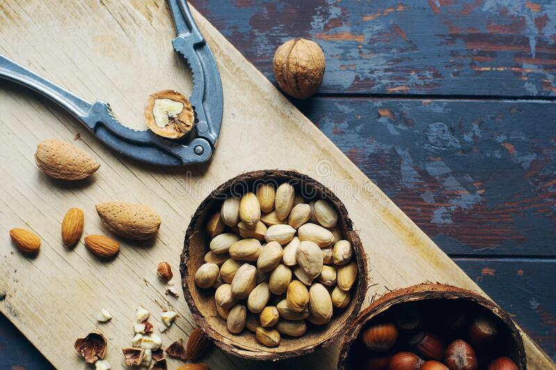 Mix of nuts in coconut bowls on dark wooden table, walnuts, almond, hazelnut, cashew, healthy various superfoods. Mix of nuts in coconut bowls and vintage royalty free stock photography