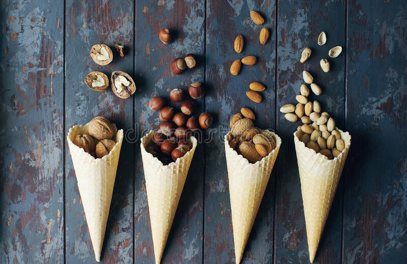 Mix of nuts in cones on dark wooden table, walnuts, almond, hazelnut, cashew, healthy various superfoods. Top view, selecitve focus stock photography