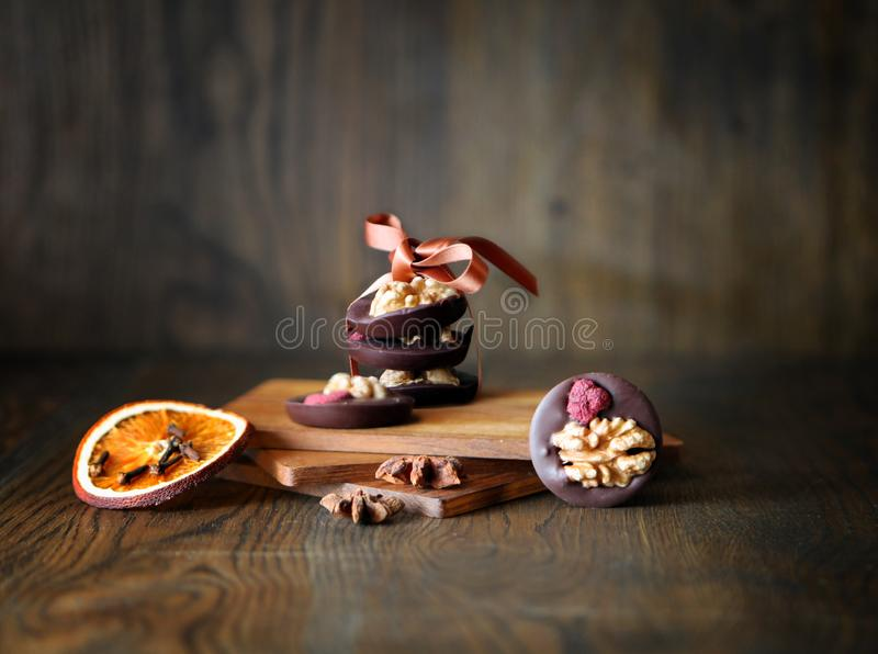Mix nuts, dry fruits and chocolate candies rings on a dark wooden background. rustic style. tasty sweeties. Mix nuts, dry fruits and chocolate on a wooden stock photo