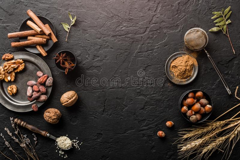 Mix of nuts and spices for baking cakes in bowl and spoon, cinnamon, star anise, hazelnuts, walnuts, wheat, lavender on dark table royalty free stock photo