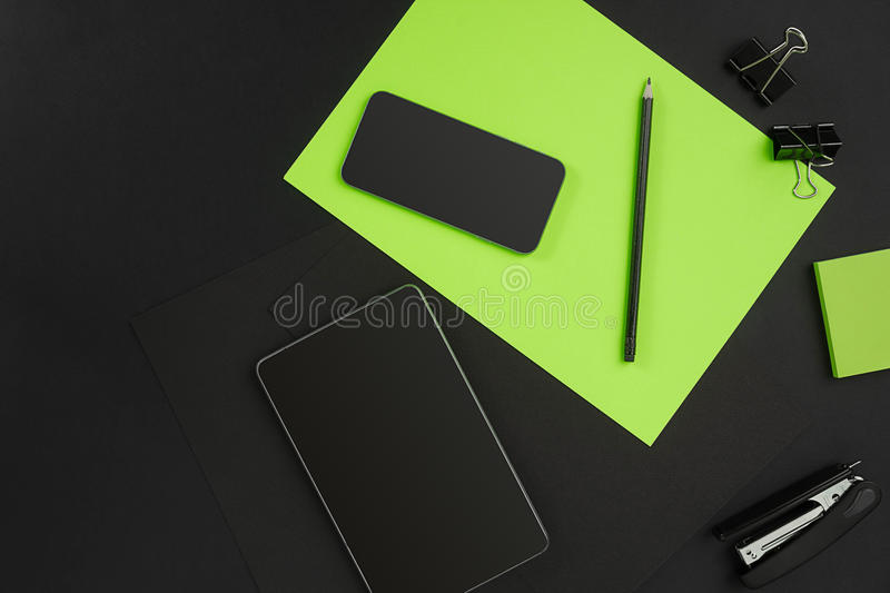 Mix of office supplies on a modern desk. Mix of office supplies on a modern office desk. Black object on a black background. Top view. Still life. Copy space stock photos