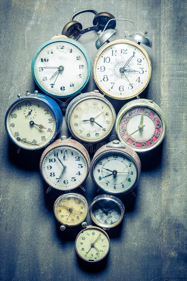Mix of old clocks in pile in wooden table. Mix of old clocks in pile on wooden table stock photography