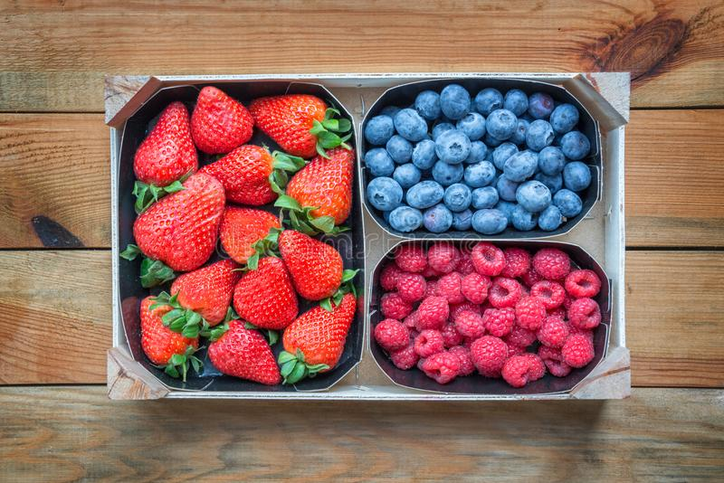 Mix of organic berries. Baskets of fresh raspberries, blueberries,strawberries on wooden table royalty free stock image