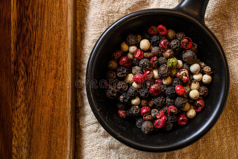 Mix of peppercorns in black bowl on linen cloth closeup near wooden board top view layflat. Ground Black, white and pink rose peppers in bowl assorted and spicy stock images