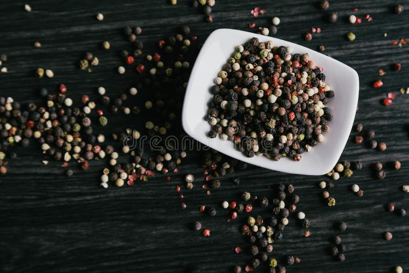 Mix of peppercorns in white bowl on wooden background royalty free stock image
