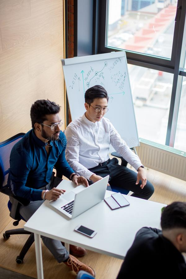 Mix raced business group analyzing reports and planning next sales period. Image of two young Indian and Asian colleagues interacting, sitting beside each other stock images