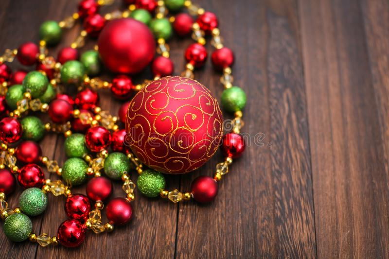 Mix of red, green, and golden Christmas balls. New Year decor for tree on dark wooden background stock images