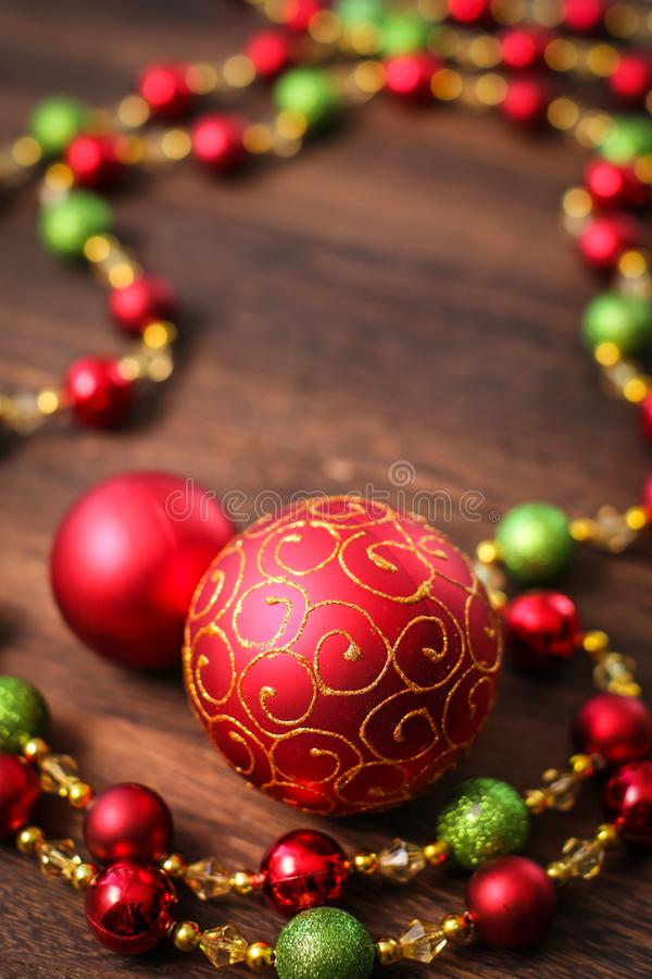 Mix of red, green, and golden Christmas balls. New Year decor for tree on dark wooden background stock photography