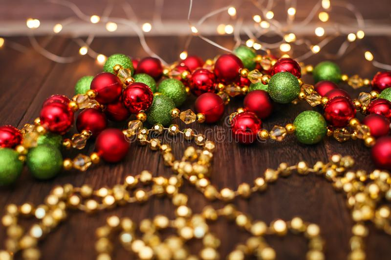 Mix of red, green, and golden Christmas balls. New Year decor for tree on dark wooden background royalty free stock image