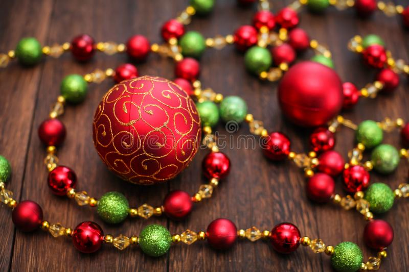 Mix of red, green, and golden Christmas balls. New Year decor for tree on dark wooden background royalty free stock images