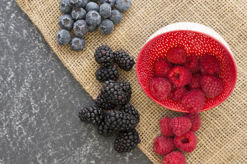 Mix of Red raspberries falling from a ceramic plate and a bunch of blackberries and blueberries in a rattan and black background. stock image