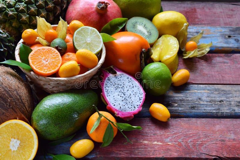 Mix of ripe tropical fruits with avocado, mango, coconut, carambola, banana, kumquat, pitahaya, kiwi Superfood background. Mix of ripe tropical fruit with stock images