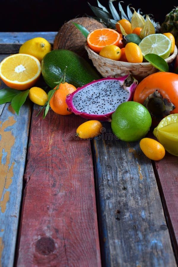 Mix of ripe tropical fruits with avocado, mango, coconut, carambola, banana, kumquat, pitahaya, kiwi Superfood background. Mix of ripe tropical fruit with stock image