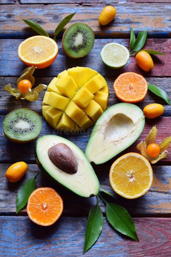 Mix of ripe tropical fruits with avocado, mango, kumquat, kiwi, citrus. Superfood background. Vegetarian raw food. Copy space. Mix of ripe tropical fruit with stock photography