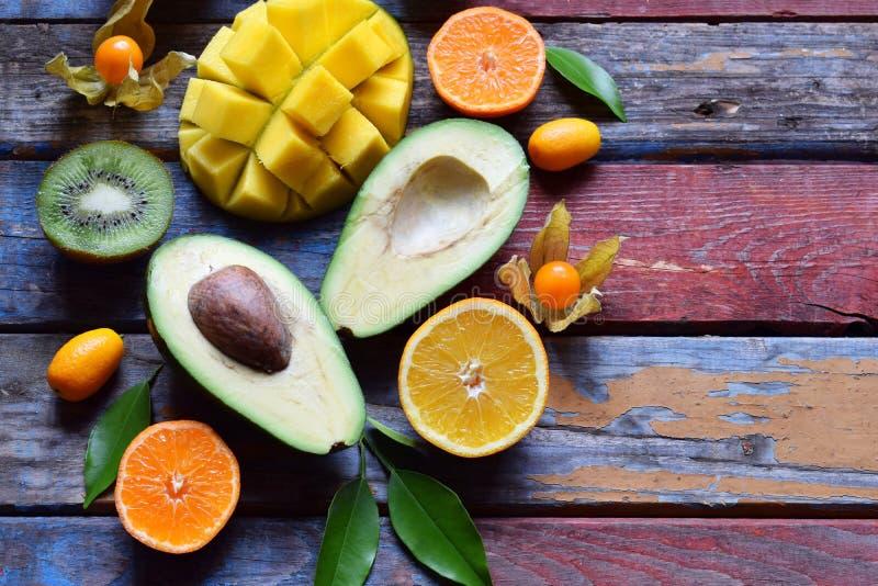 Mix of ripe tropical fruits with avocado, mango, kumquat, kiwi, citrus. Superfood background. Vegetarian raw food. Copy space. Mix of ripe tropical fruit with stock image